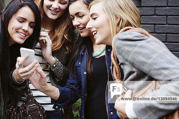 Glückliche Freundinnen schauen aufs Handy