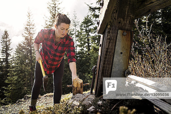 Woman cutting wood with axe on field
