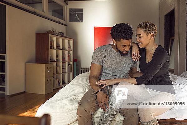 Glückliches junges Paar sitzt zu Hause auf dem Bett