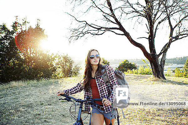 Young woman with bicycle and backpack walking on field