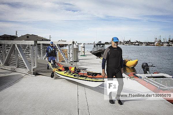 Ältere Männer tragen Kajaks  während sie auf dem Pier am Fluss gehen