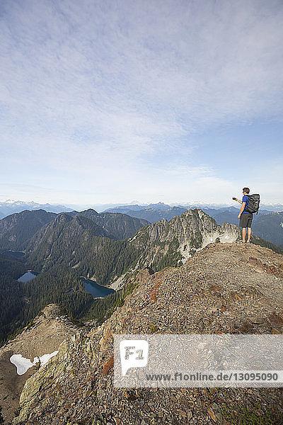 Wanderer fotografiert in voller Länge  während er auf einer Klippe gegen den Himmel steht