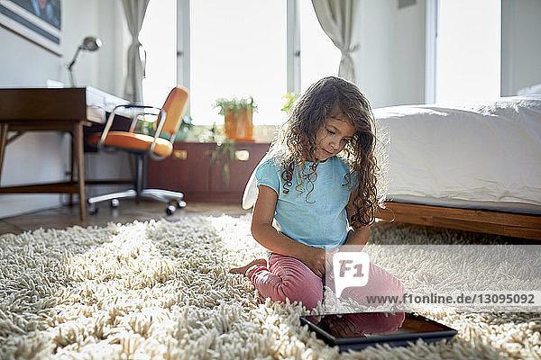 Mädchen benutzt Tablet-Computer  während sie im Schlafzimmer auf dem Teppich kniet