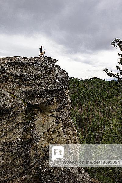 Niedrigwinkelansicht von Mensch und Hund  die auf einer Klippe vor bewölktem Himmel stehen