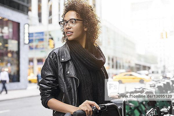 Frau mit Brille schaut weg,  während sie auf dem Parkplatz steht