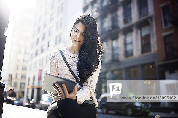 Schöne Frau benutzt Tablet-Computer,  während sie an einem sonnigen Tag an einer Straße in der Stadt sitzt