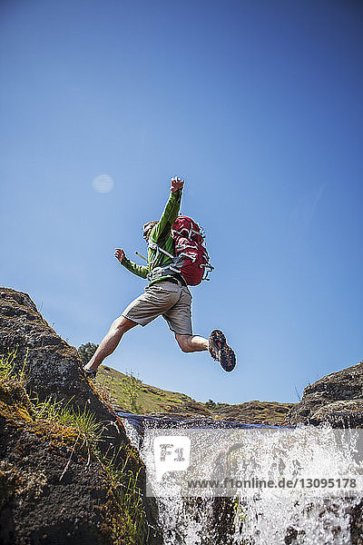 Carefree hiker jumping over stream against clear sky