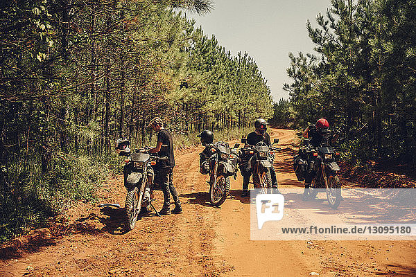 Bikers with motorcycles resting on dirt road during sunny day