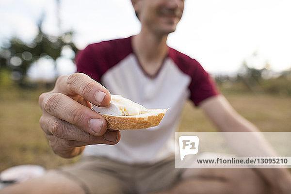 Ein Mann hält Brot in der Mitte  während er auf dem Feld sitzt Ein Mann hält Brot in der Mitte, während er auf dem Feld sitzt