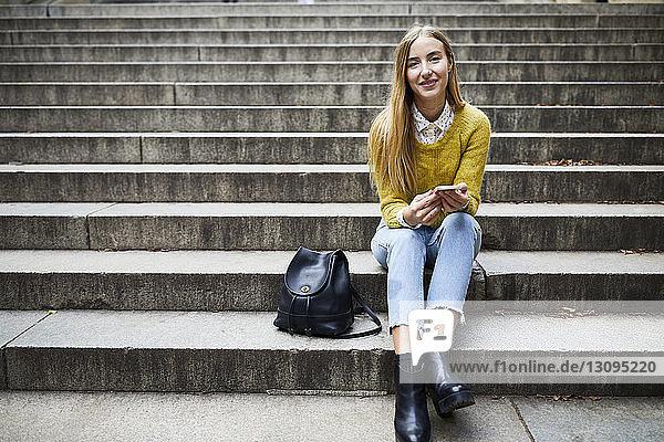 Porträt einer lächelnden jungen Frau  die auf Stufen im Park sitzt