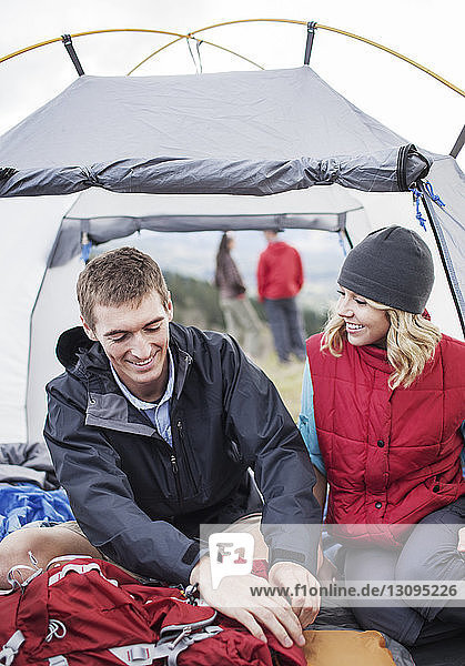 Happy woman looking at man while sitting in tent