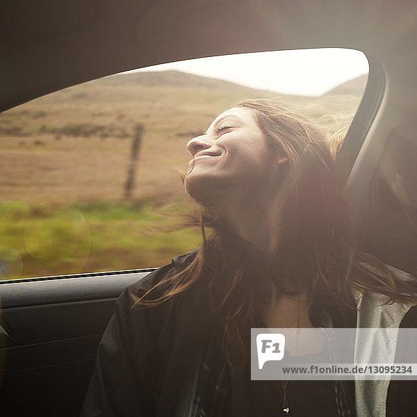 Carefree woman enjoying road trip in car at countryside