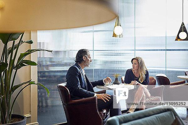 Geschäftsleute unterhalten sich  während sie in der Cafeteria im Kreativbüro sitzen