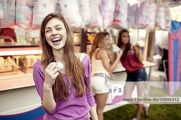 glückliches Teenager-Mädchen hält Zuckerwatte mit Freunden im Hintergrund