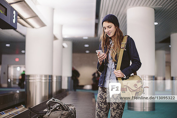 Woman using mobile phone while standing by baggage claim at airport