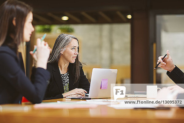 Female colleagues planning in meeting at board room