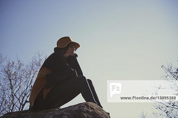 Tiefwinkelansicht einer nachdenklichen Frau  die auf einem Felsen gegen den Himmel sitzt