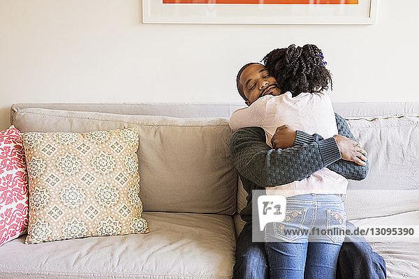 Mann umarmt Tochter  während er auf Sofa sitzt