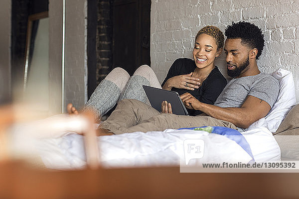 Happy multi-ethnic couple using tablet computer on bed