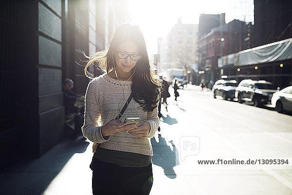 Junge Frau hört Musik über Smartphone auf der Straße
