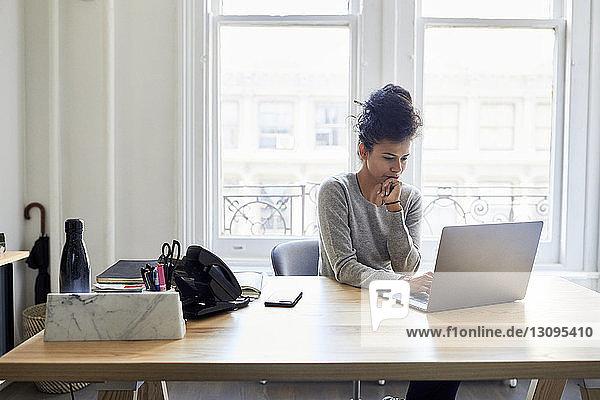 Seriöse Geschäftsfrau benutzt Laptop-Computer am Schreibtisch gegen Fenster im Büro