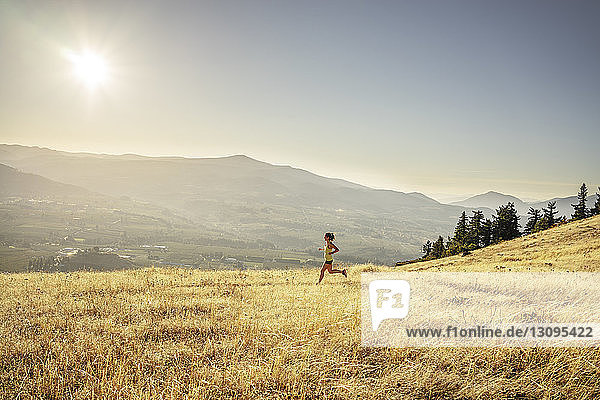 Side view of woman jogging on grassy field against sky during sunny day