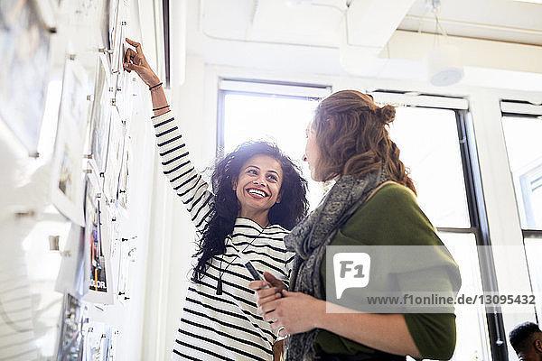 Lächelnde Geschäftsfrau schaut eine Kollegin an  während sie am Schwarzen Brett im Büro steht