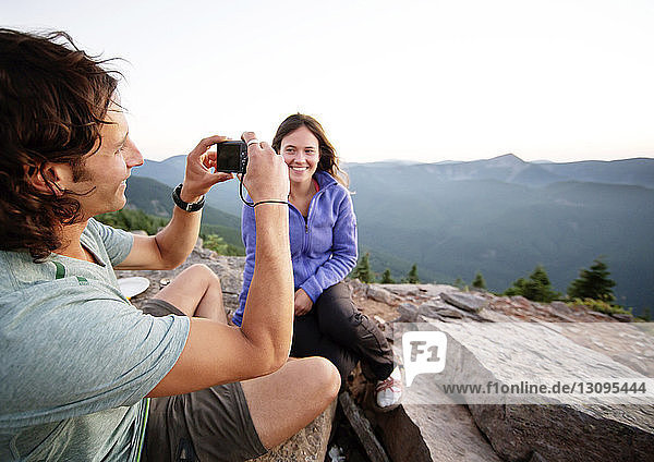 Frau betrachtet Freund beim Fotografieren  während sie auf Berg sitzt