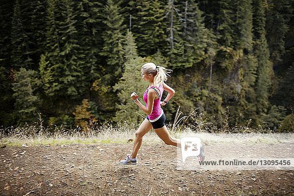 Hochwinkelaufnahme einer auf dem Feld laufenden Athletin