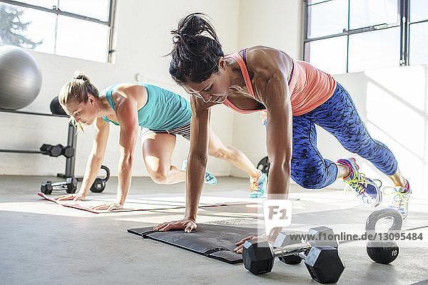 Female athletes doing push-ups on exercise mats in gym