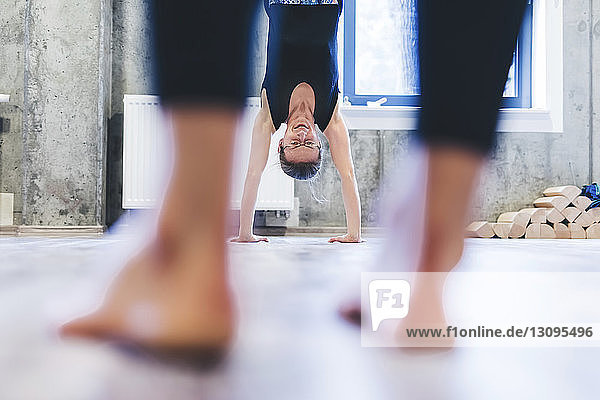 Yogalehrerin macht Handstand  während die Frau in der Turnhalle im Vordergrund steht
