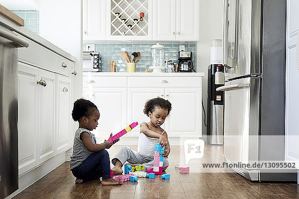 Sisters playing with toy blocks while sitting on hardwood floor in kitchen at home