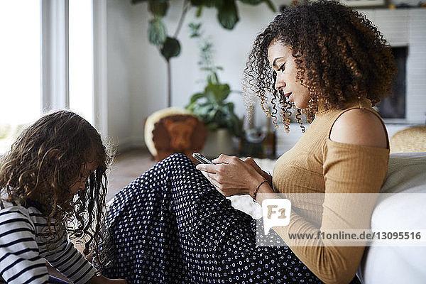 Mutter benutzt Mobiltelefon  während sie mit der Tochter am Sofa zu Hause sitzt