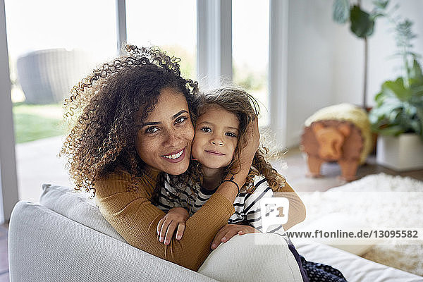 Portrait of mother embracing daughter while sitting on sofa at home