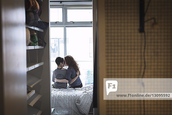 Romantic lesbian couple sitting on bed at home
