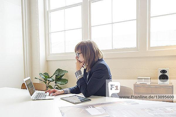 Geschäftsfrau benutzt Laptop-Computer  während sie im Büro am Schreibtisch sitzt