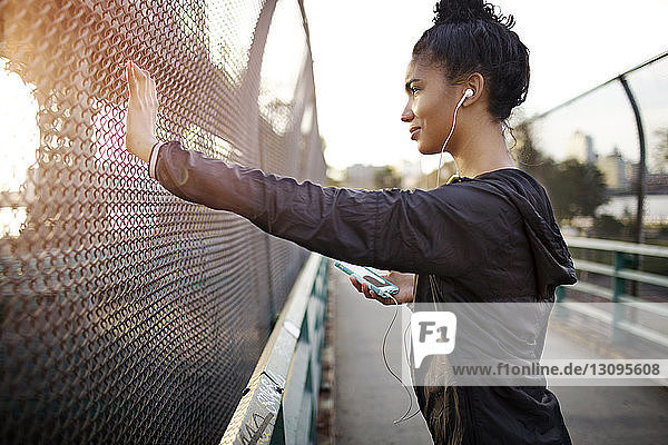 Side view of sporty woman listening to music while standing by fence