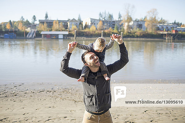 Happy father carrying daughter on shoulders while standing at Brae Island Regional Park