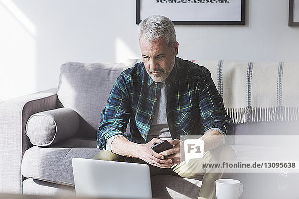 Mature man using laptop while sitting on sofa at home