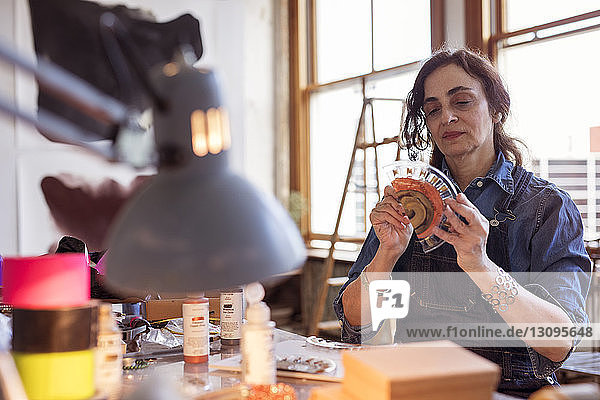 Female artist painting glass design in workshop