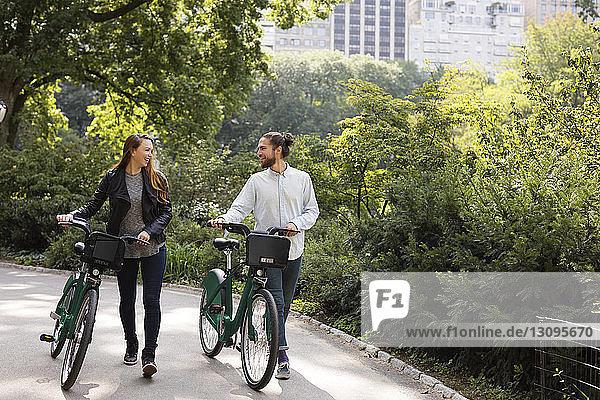 Paar redet während des Gehens auf einem Fußweg mit Fahrrädern