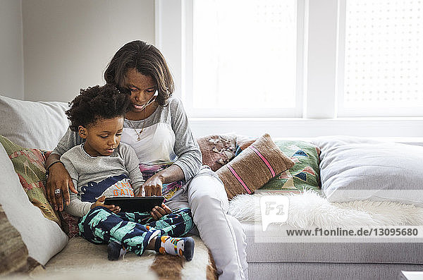 Mother and son using tablet computer on sofa at home