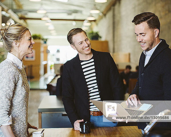Businessman using laptop computer while standing with colleagues in office