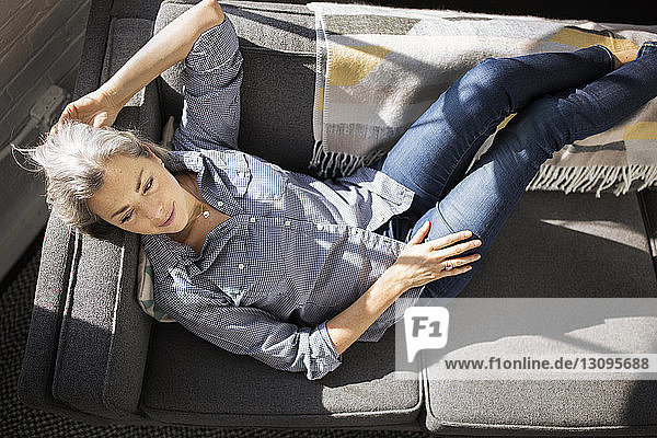 Overhead view of thoughtful woman relaxing on sofa at home