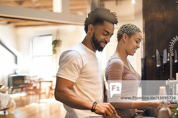 Glückliches multiethnisches Ehepaar bereitet gemeinsam Essen in der Küche zu