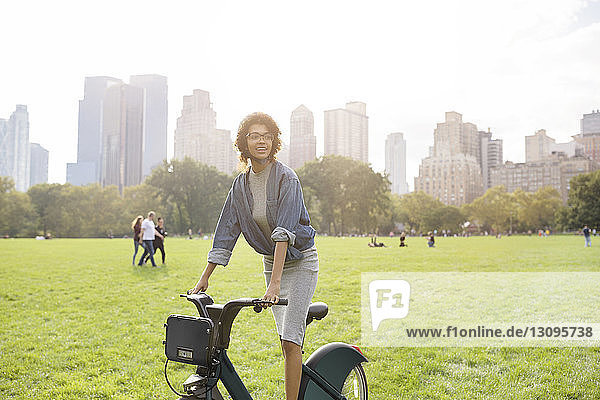 Woman looking away while riding bicycle on field against clear sky
