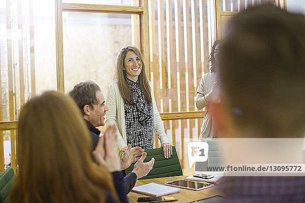 Business people applauding for businesswoman standing by chair in board room at office