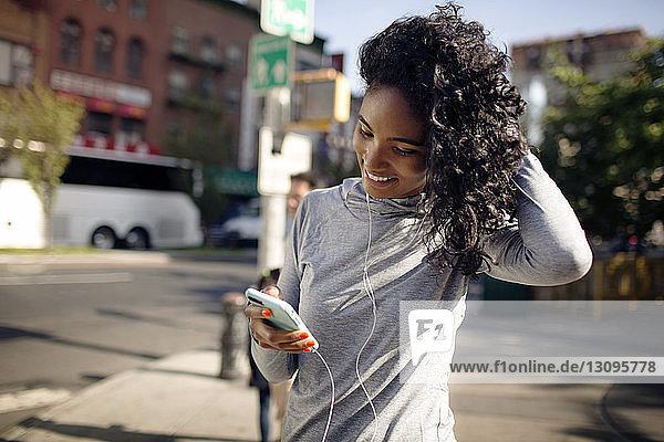 Glückliche Frau benutzt Smartphone  während sie auf der Straße steht