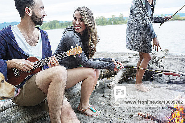 Woman looking at playing ukulele while sitting by campfire against river