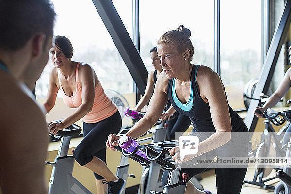 Männlicher Ausbilder führt Frauen auf Heimtrainern im Fitnessstudio